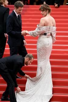 Die Treppen in Cannes haben es in sich. Auch Milla Jovovich benötigt Hilfe. Und das von gleich zwei Assistenten.