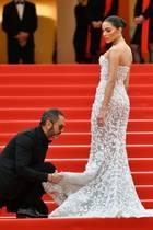 """Kurz bevor die Fotografen """"losschießen"""", springt Olivia Culpos Assistent ihr zur Seite und richtet ihr Kleid mit extremer Genauigkeit. Jeder Millimeter soll hier stimmen."""