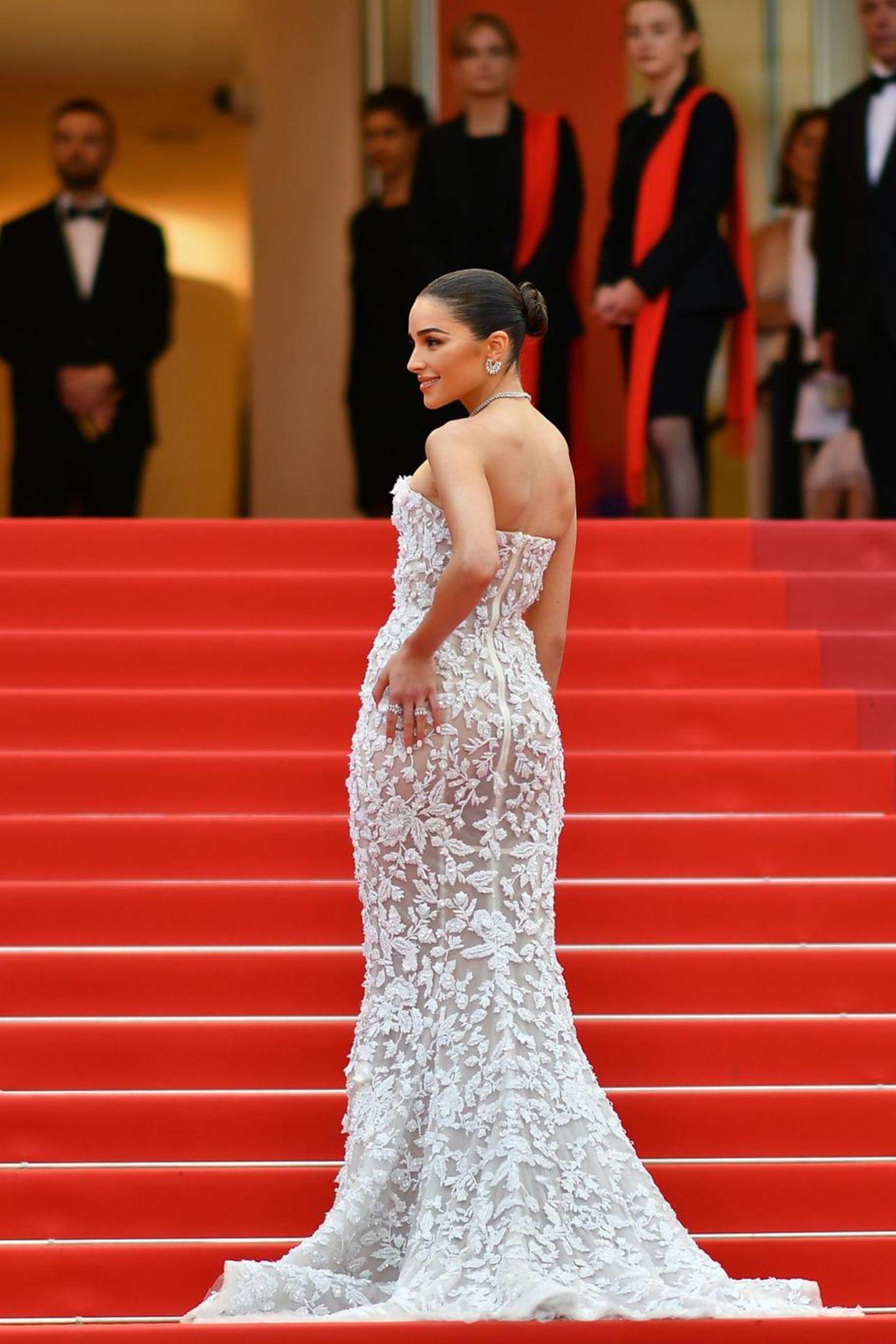 Bevor Olivia Culpo in den Filmpalast von Cannes verschwindet, posiert sie noch einmal für die Fotografen. Ihr Kleid fällt dabei zauberhaft an ihrem Körper herunter und fächert sich auf dem Boden perfekt. Zufall? Keinesfalls.