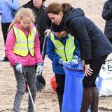Herzogin Catherine hilft Kindern dabei, den Strand vonNewborough von Algen zu befreien.
