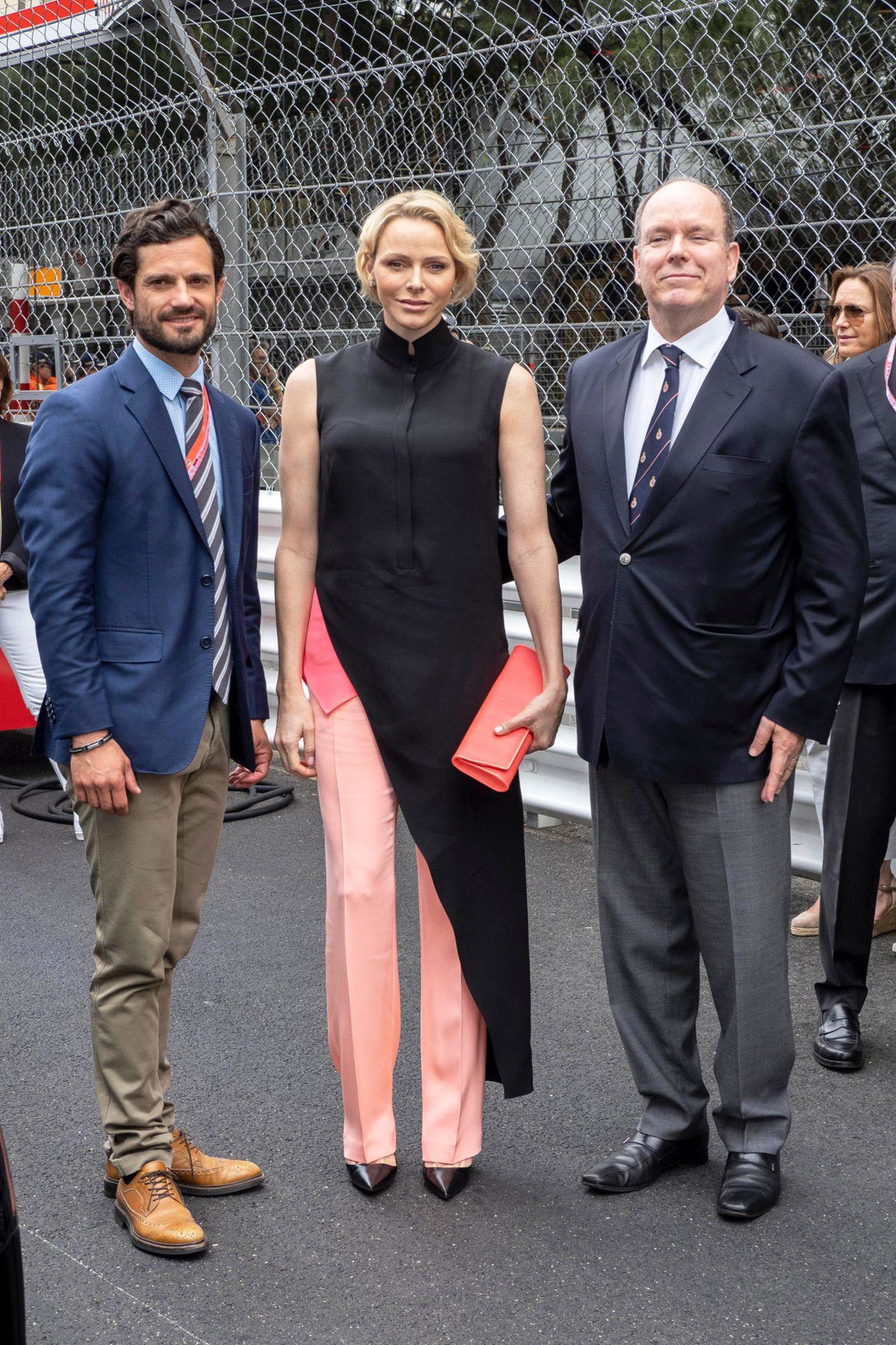 Bei der Siegerehrung beim großen Preis von Monaco greift Fürstin Charlène erneut zu Pinktönen und zum Label Akris. Die Fürstin trägt einen Look direkt vom Laufsteg. Zu einer pinkfarbenen Hose kombiniert sie ein Top in einem leicht dunkleren Pinkton und ein schwarzes, asymmetrisches Top.