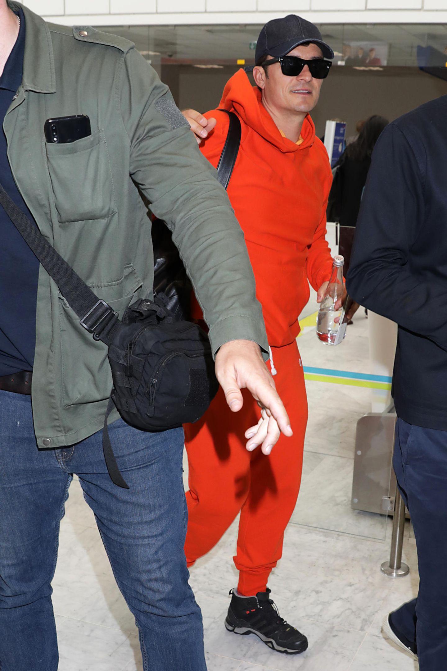 Orlando Bloom versteckt sich am Flughafen von Nizza zwar hinter einer großen, schwarzen Sonnenbrille und trägt sein Basecap tief ins Gesicht gezogen – erkannt haben ihn Paparazzi aber trotzdem. In einem knallroten Trainingsanzug und bequemen Sneakerngeht es fürden Hollywood-Star zum Check-in, bevor er den Heimflug zurück in die USA antreten kann.