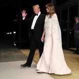Melania trägt ein bodenlanges Capekleid mit edlen Feder-Applikationen des Labels J.Mendel. Mit knapp 5.000 Euro mal wieder ein echter Luxuslook. Dazu kombiniert die First Lady silberfarbene High-Heels.