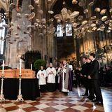 Der Dompfarrer spricht Gebete aus und segnet den Verstorbenen. Andächtig steht Laudas Witwe Birgit mit den Söhnen ihres toten Mannes, Lukas und Mathias, vor dem Sarg.