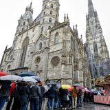 Trotz strömenden Regens stehen die Menschen vor dem Wiener Stephansdom Schlange.