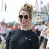 Auf dem Glastonbury-Festival, kann das Wetter schon mal rau werden. Schauspielerin Lily James hält sich mit einem lässigen Messy Bun die Haare aus dem Gesicht.