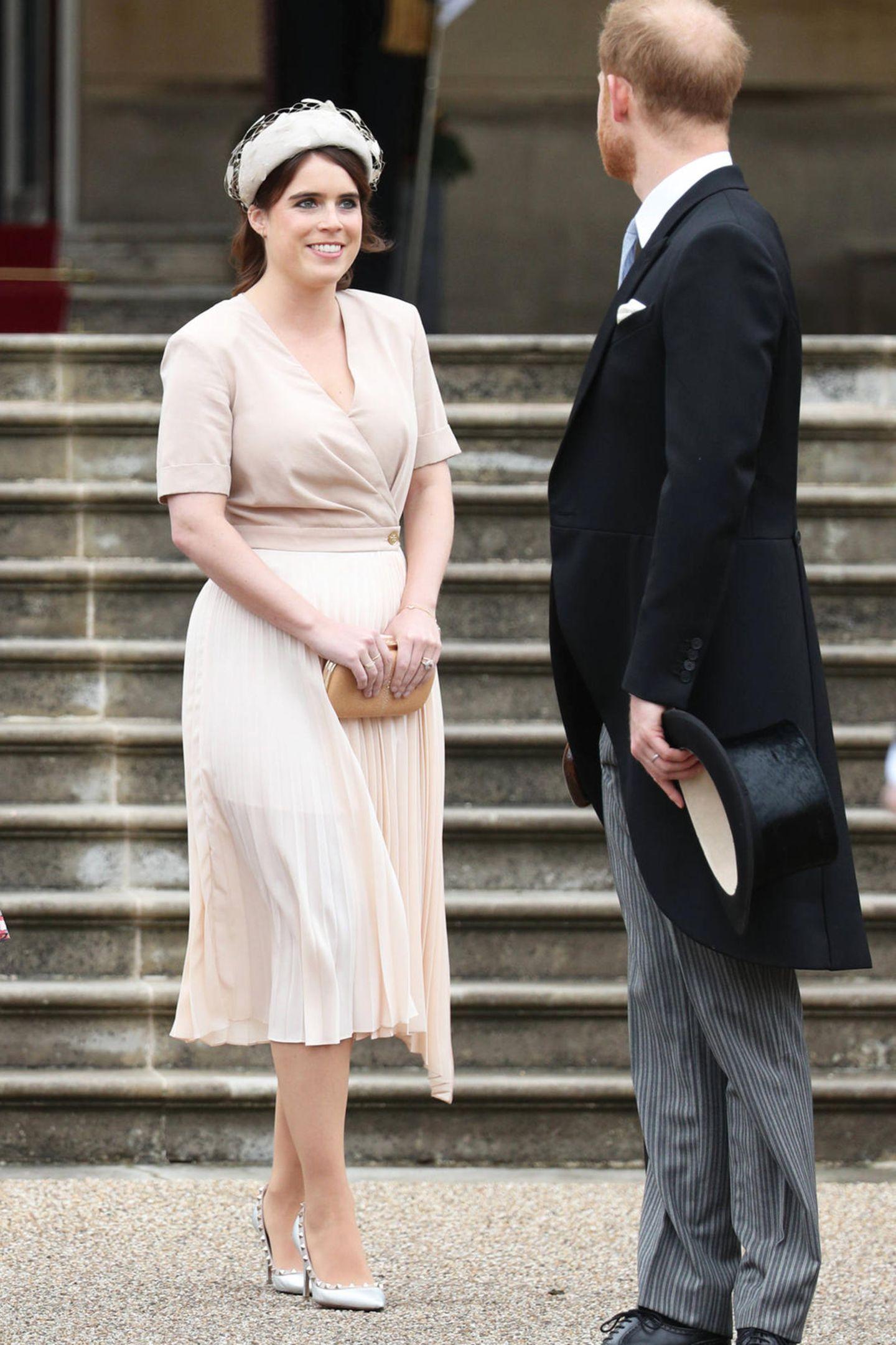 Im Rahmen der Royal Garden Party 2019 im Buckingham Palast zeigen sich Prinzessin Eugenie und Prinzessin Beatrice an der Seite ihrer Großmutter der Queen in Looks, die unterschiedlicher nicht sein könnten. Eugenie wählte ein semitransparentes Kleid von Sandro für rund 295 Euro.