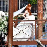 Da kommt die Braut! Wunderschön im floralen Hochzeitskleid mit langer Schleppe und langem Schleier schreitet Barbara Meier auf dem blumengeschmückten Steg Richtung Altar.
