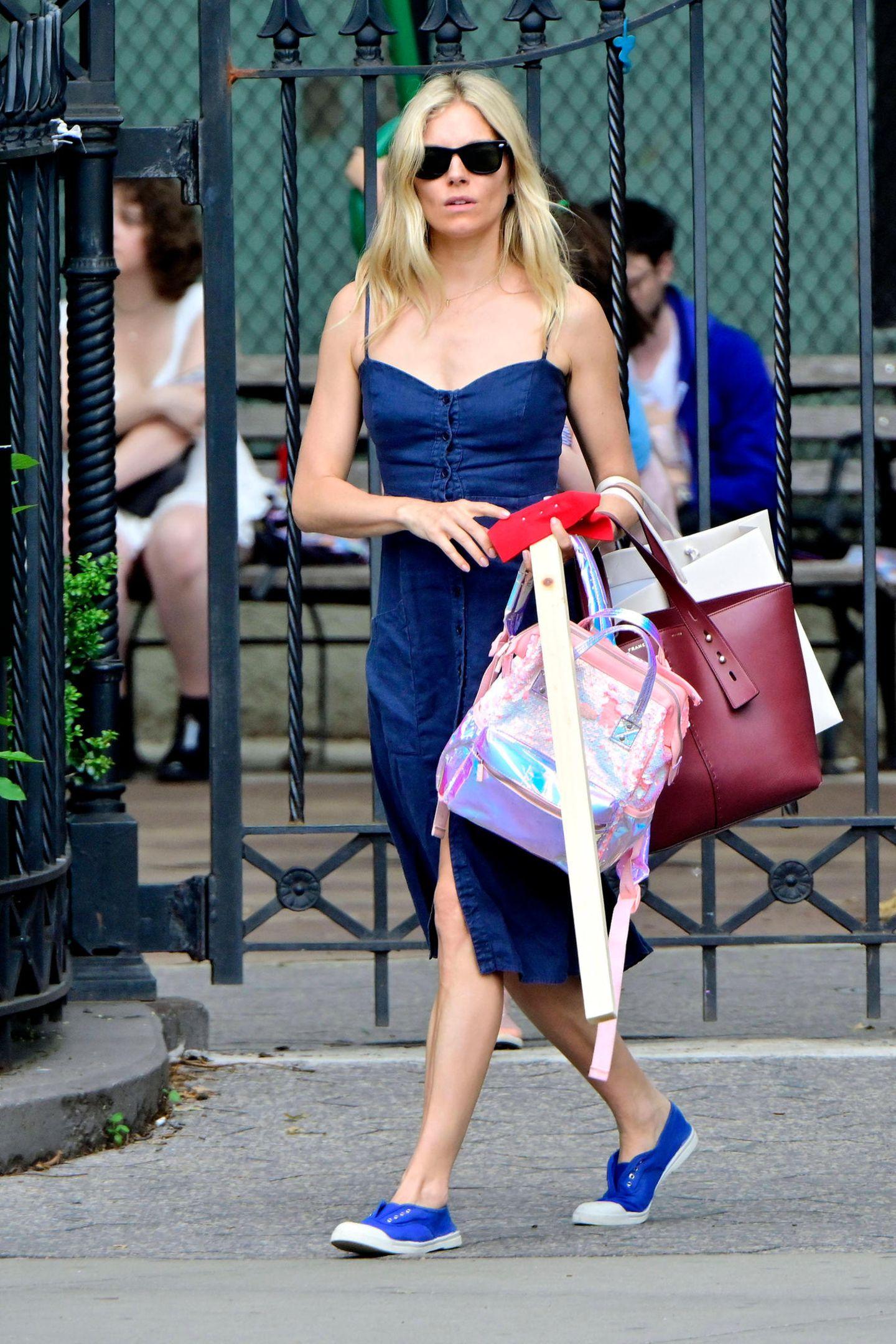 Ganz schön schlicht aber dafür umso cooler ist Sienna Miller unterwegs. Sie trägt ein Jeanskleid mit feinen Trägern, das in der Front geknöpft wird und mit einem Herzausschnitt bezaubert.