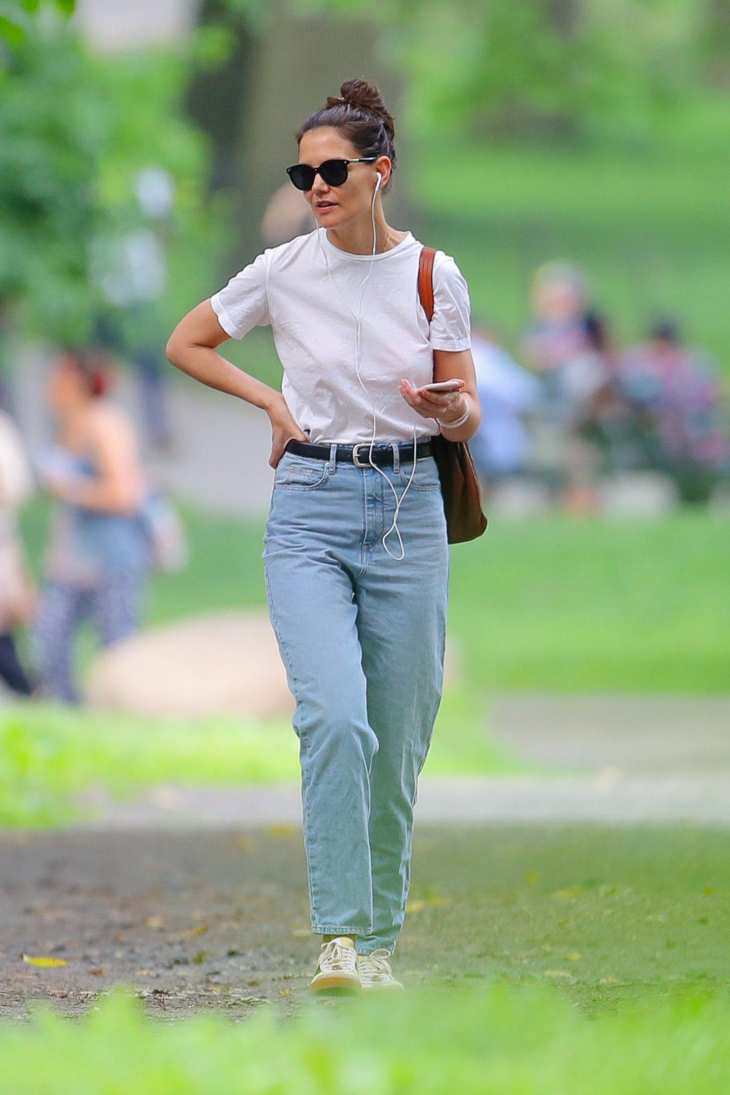 """Sonntags im Central Park: Katie Holmes schlendert ganz gemütlich durchs Grüne. Da muss auch der Look passen. Der Weltstar schlüpft in eine ganz simple Kombination aus weißem Shirt und Mom-Jeans. Mit Sonnenbrille auf der Nase fällt sie so überhaupt nicht auf und kann einen """"normalen"""" Tag genießen."""