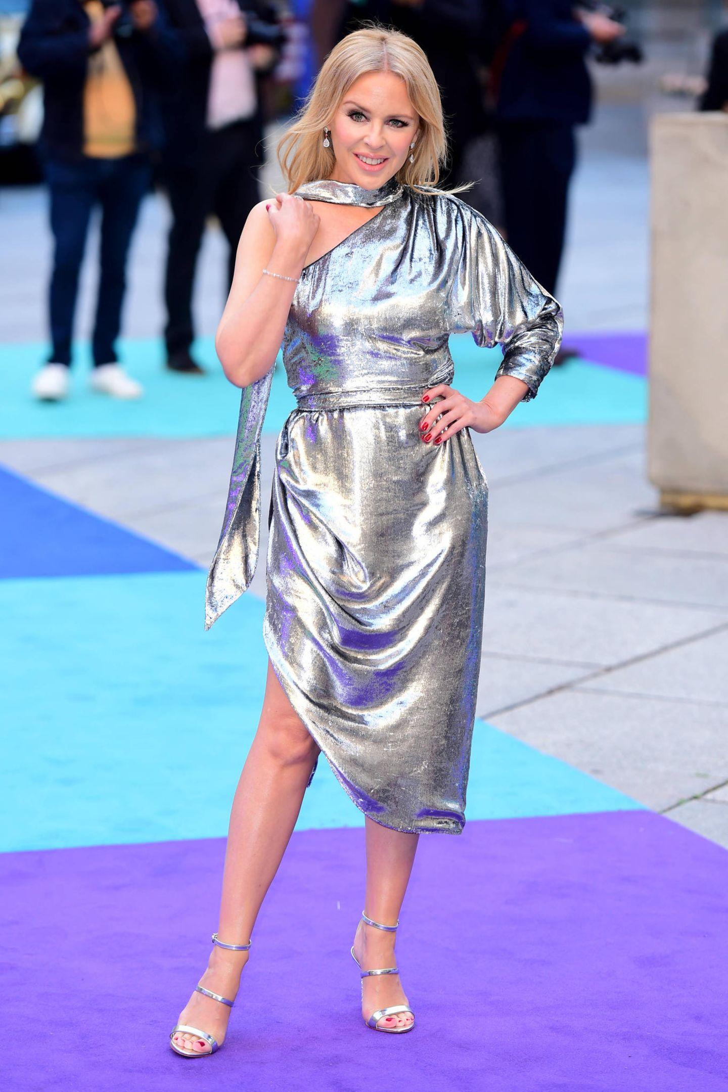 Bitte wie alt soll Kylie Minogue laut Geburtsurkunde sein?! Die australische Sängerin, die Ende Mai 2019 ihren 51. Geburtstag feierte, sieht im asymmetrischen Metallic-Kleid einfach umwerfend aus.