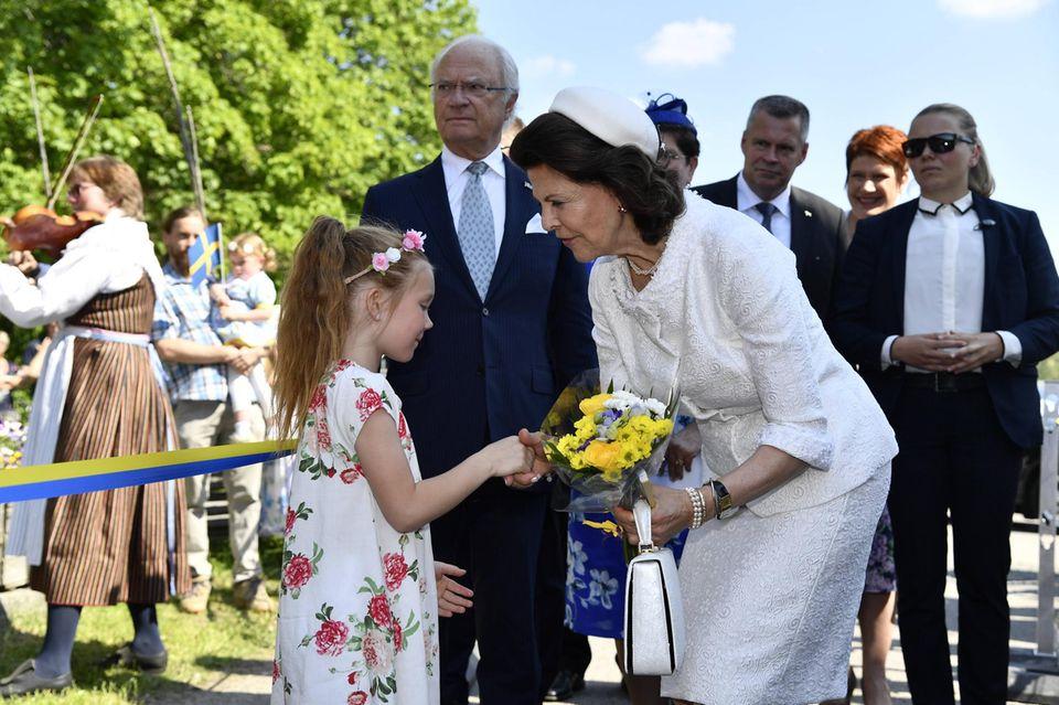 Ein kleines Mädchen überreicht Königin Silvia einen Strauß Blumen.