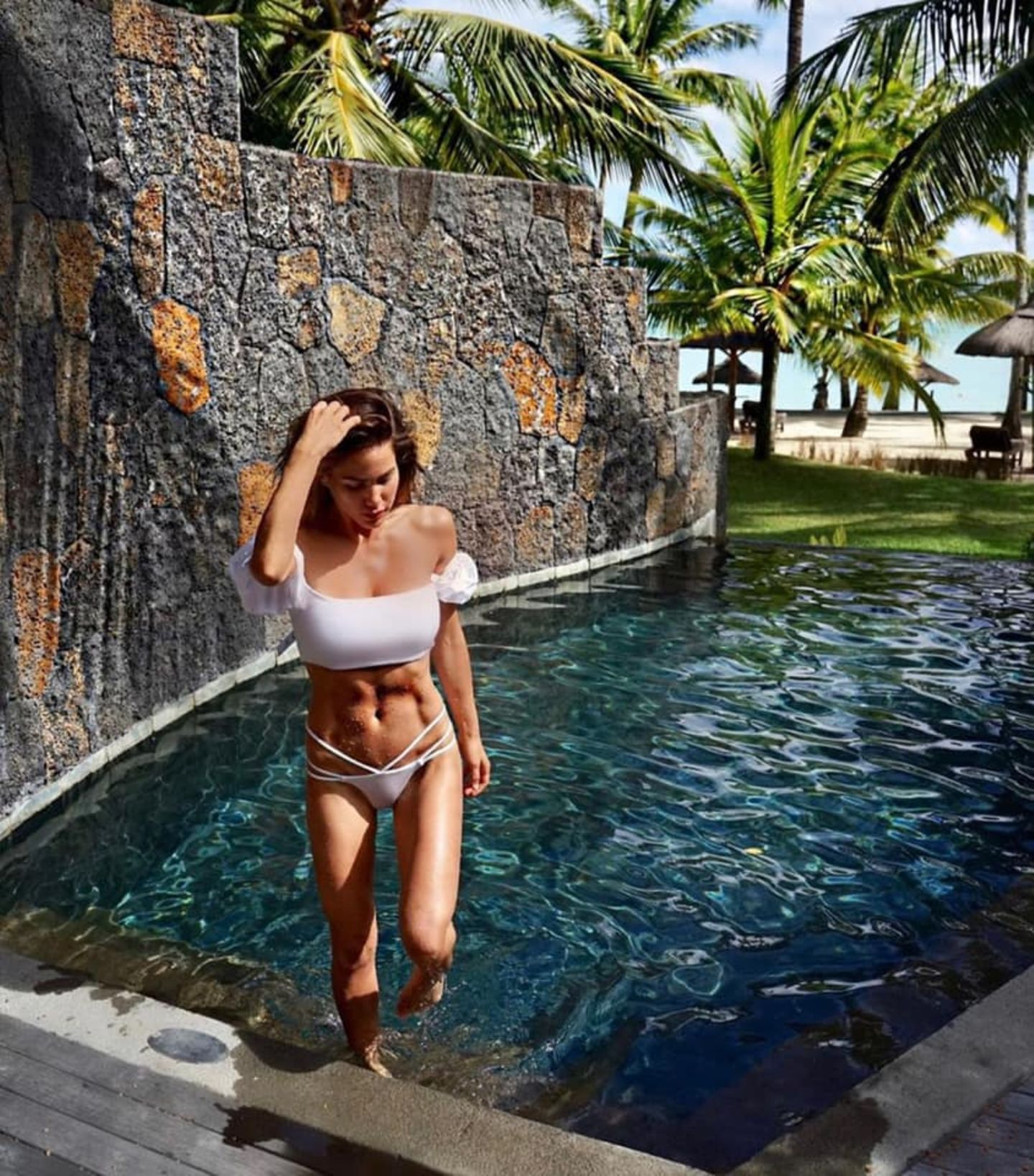 Steinhart wie die Wand im Hintergrund ist mittlerweile auch der Bauch von Angelina Heger, die seit einigen Monaten stark an ihrer Figur arbeitet. Um ihre Muskeln nicht zu verbergen, wählt sie einen Bikini statt Badeanzug. Während das Oberteil durch die Bardot-Puffärmel relativ niedlich wirkt, ist das Höschen ein sexy Modell mit Straps.