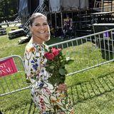 Mit einem Strauß Rosen in der Hand lächelt die schwedische Kronprinzessin in die Kamera.