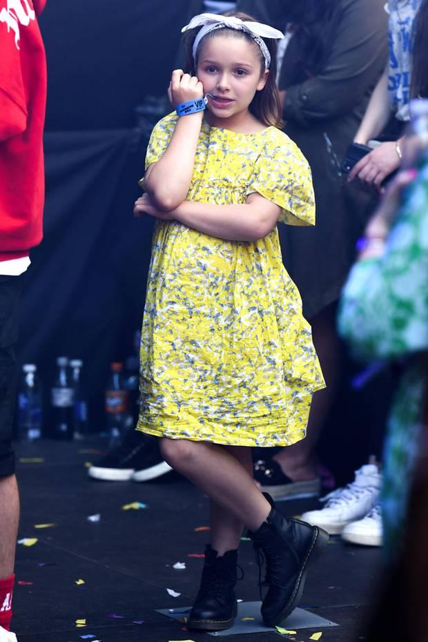 """Süßer Star-Spross im Festival Look: Beim """"Capital's Summertime Ball"""" im Wembley Stadionin London kaut Harper Beckham beherzt auf ihrem VIP-Bändchen. Ihr Haar hat die Tochter von Victoria Beckham lässig mit einem Tuch nach hinten gebunden. Zu ihrem gelben Sommerkleidchen kombiniert sie derbe Booties. Eine echte Mini-Fashionista!"""