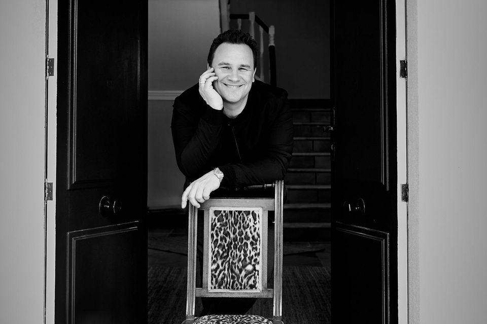 An der Eingangstür präsentiert Guido Maria Kretschmer sein Lieblingsmöbel: Auf diesem Stuhl lernte er als Kind schreiben. Den ursprünglichen Polsterbezug ließ er später durch Animal-Print ersetzen