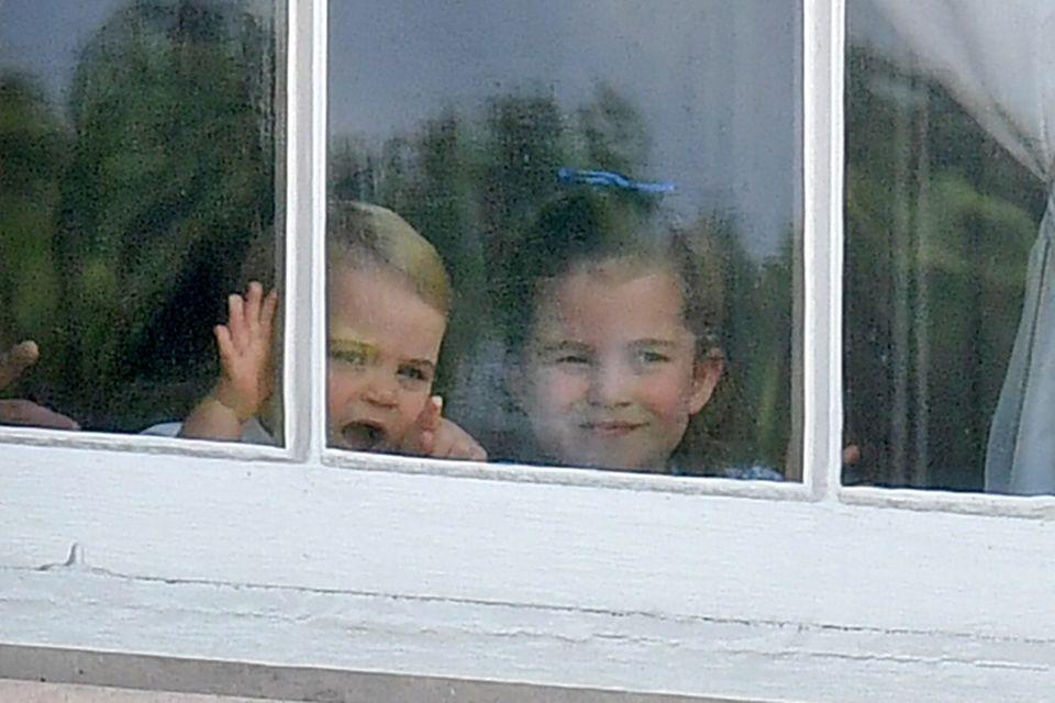 Schelmisch grinst Prinzessin Charlotte hinter den Fensterscheibendes Palasts, ihr Haar hat sie mittig hochgesteckt und eine blaue Schleife ziert ihren Kopf.