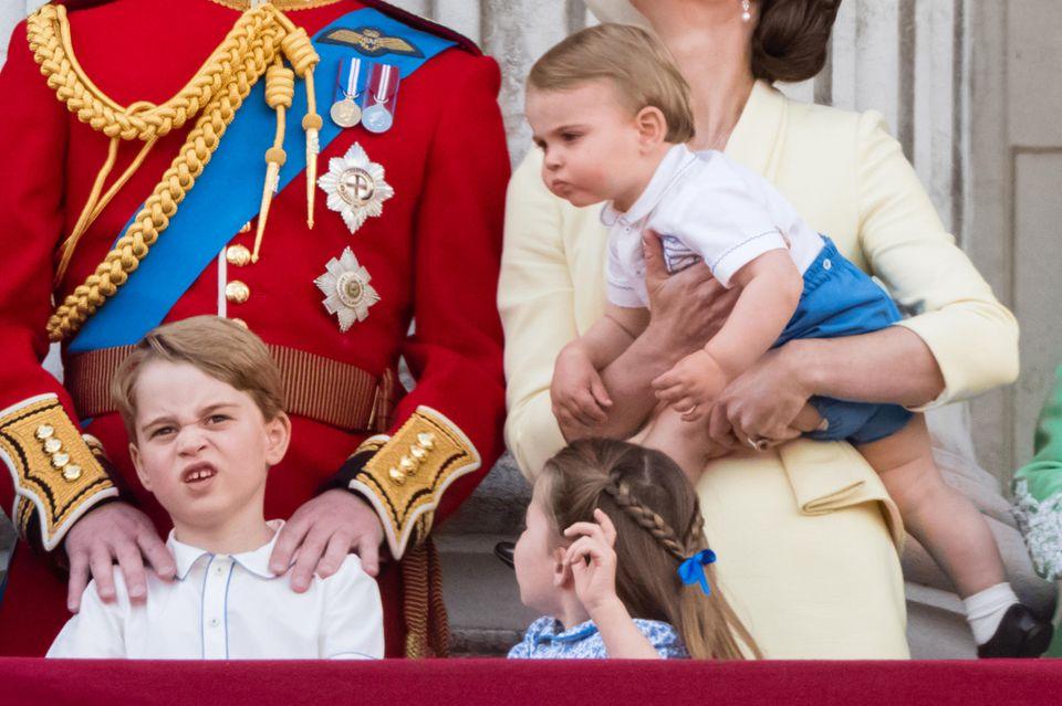 Auf dem Balkon zeigt sich Prinzessin Charlotte mit zwei geflochtenen Zöpfen, die von ihrer blauen Schleife zusammengehalten werden.