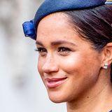Herzogin Meghan trägt ebenfalls einen tief sitzenden, seitlichen Dutt - jedoch weniger aufwendig gestylt. Hingucker ist ihr kleiner Fascinator-Hut, der stark an den Hut erinnert, den ihre Mutter Doria zu Meghans Hochzeit trug.