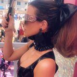 Passend zum Outfit ziert eine große schwarze Schleife ihr Haar, die Fingernägel sind schwarz bemalt.