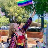 Auf der Pride Parade schwenkt sie eine große Regenbogenflagge.
