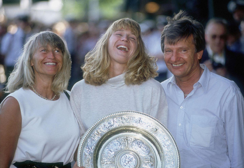 Mit ihren Eltern Heidi und Peter Graf freut sich Steffi 1991 über ihren Wimbledon-Sieg. Nur wenige Jahre später wird Peter Graf wegen Steuerhinterziehung verurteilt.Er verliert in dem Zuge seinen Posten als Steffis Manager. 1999 folgt die Scheidung von Heidi und Peter Graf.