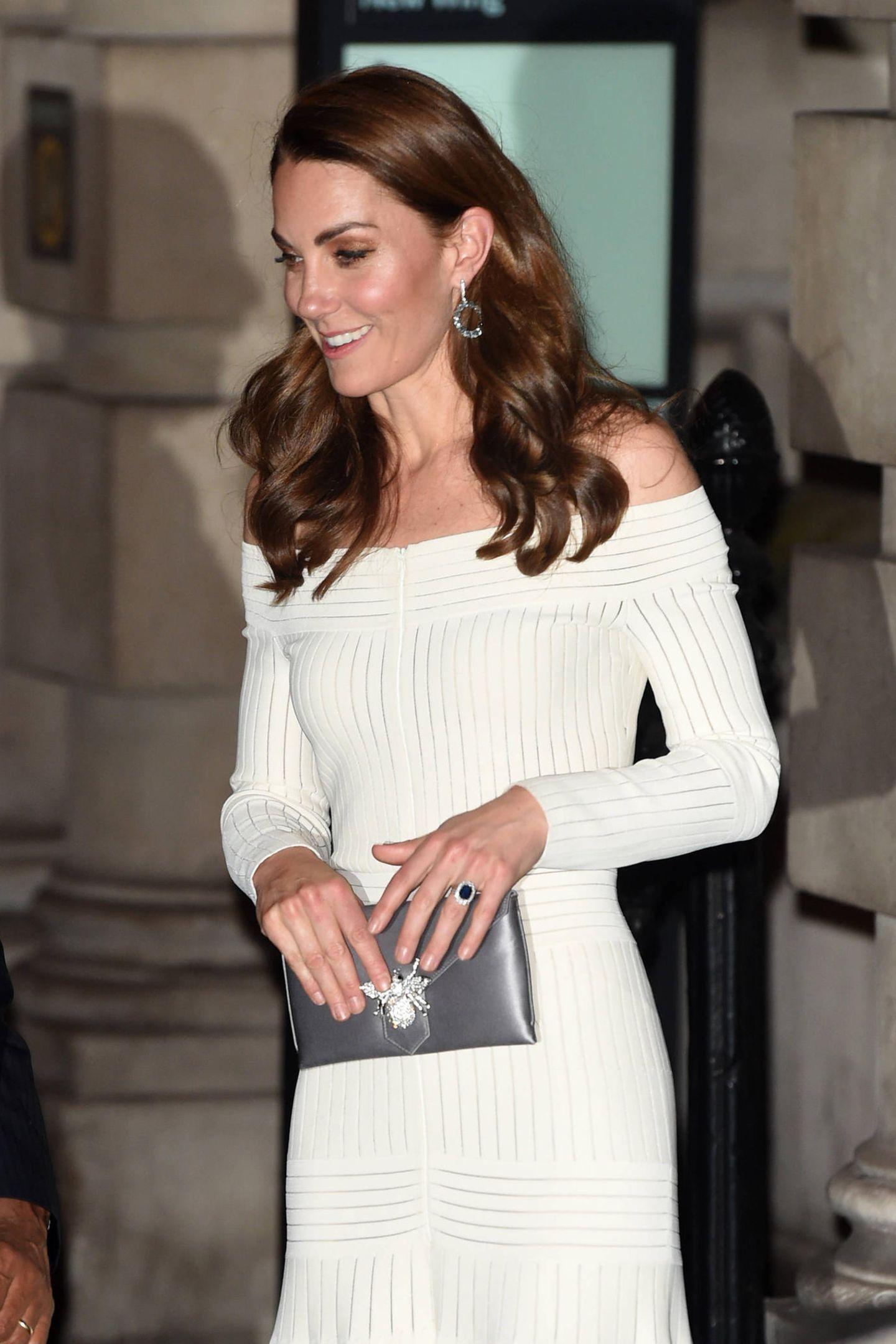 Im Juni 2019 greift Herzogin Catherine zu einem Kleid aus hellem Strick, das ganz besonders zu ihrer Frisur einfach fantastisch aussieht. Ihre dunklen Wellen stehen in einem herrlichen Kontrast zu dem Stoff und liegen locker auf ihren freien Schultern auf.