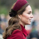 """Einen """"halben Zopf"""" trägt Herzogin Catherine auch in einer eleganteren Variante. An Weihnachten 2018 entscheidet sie sich dafür, die Seiten parallel zu ihrem Haarreif zusammenzubinden. Die Längen lockt sie hingegen."""