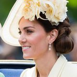 Wenn Herzogin Catherine sich für einen seitlich sitzenden Hut entscheidet, lässt sie ihr Haar zu einem tiefen Chignon zusammenbinden, der auf der anderen Seite sitzt.