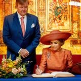 Das niederländische Königspaar trägt sich in das Gästebuch der Bibliothek ein.