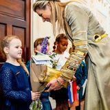 Königin Máxima nimmt Blumen entgegen, die ihr ein kleines Mädchen schenkt.