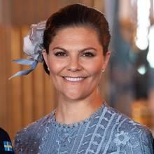 Farblich perfekt auf ihr Kleid abgestimmt, trägt Prinzessin Victoria eine Blume in hellblau in ihrem Haar, das sie hochgesteckt trägt.