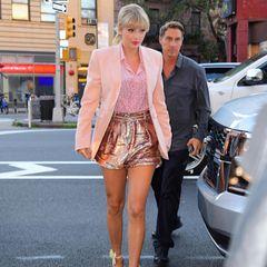 In New York erwischen Paparazzi Taylor Swift auf dem Weg in ein Hotel und fangen ihr zuckersüßes Outfit ein. Zu einer seidenen Bluse von Yves Saint Laurent für rund 740 Euro kombiniert sie einen Blazer in zartem Rosa sowie eine Glitzer-Shorts von Iro Paris. Doch anders als gedacht, ist das Discokugel-Höschen bei diesem Look nicht der Hingucker ...