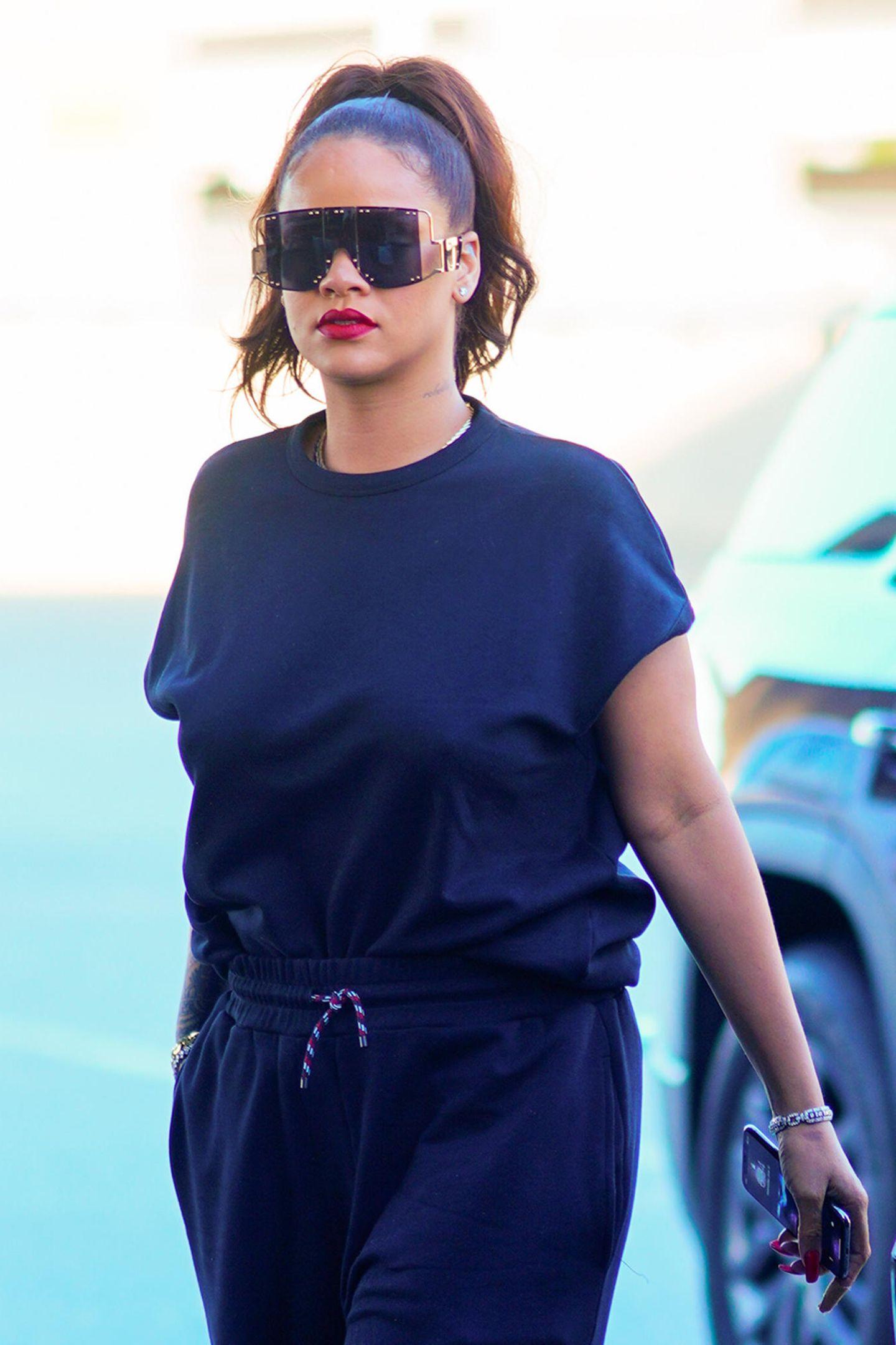 """Rihannas XXL-Sonnenbrille zieht alle Blicke auf sich. Das große Modell mit verspiegelten, schwarzen Gläsern soll zu ihrer eigenen Modelinie gehören – ein """"Fenty""""-Logo ziert das Accessoire. Mit einem hohen Pferdeschwanz setzt die 31-Jährige ihre Sonnenbrille besonders gut in Szene."""