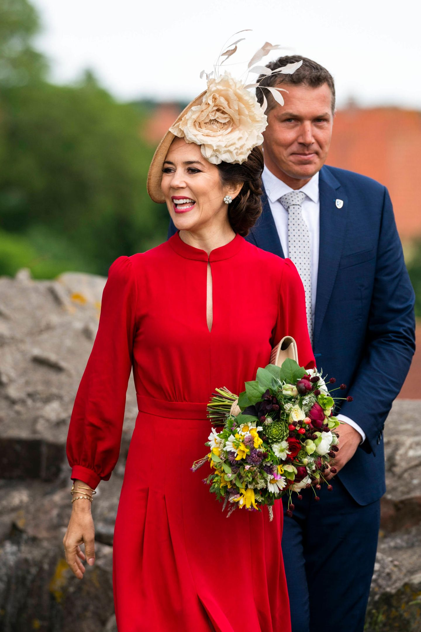 Zu ihren Pumps in Nationalfarben kombiniert Prinzessin Mary einrotesSeidenkleid von Designerin Raquel Diniz für rund 700 Euro, das sie bereits im August 2018 ausführt. Ein beigefarbener Hut mit einer großen Blüte ziert den Kopf der 47-Jährigen und macht ihren Look perfekt.