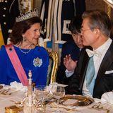 Königin Silvia ist mithilfe eines Dolmetschers ins Gespräch mit Moon Jae-in vertieft.