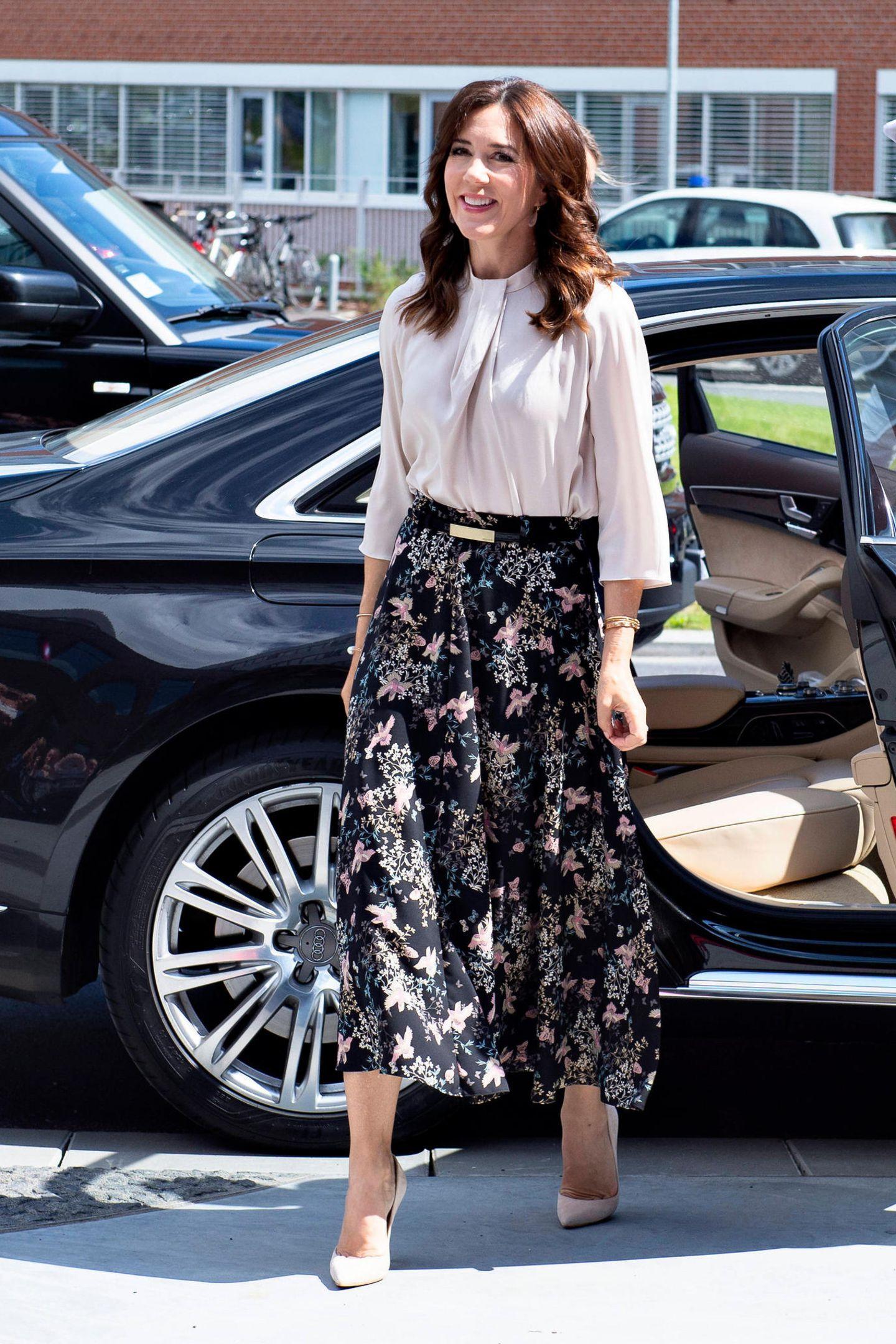 Im Rahmen eines royalen Termins inAarhus steigt Prinzessin Mary elegant aus ihrer Limousine und bezaubert wie gewohnt mit einem femininen Wow-Look. Ihr floral gemusterterMaxirock wird von ihrer beigefarbenen Bluse und den farblich abgestimmten Pumps eingerahmt.