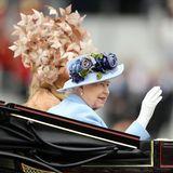 """Die royale Prozession am ersten Tag von """"Royal Ascot"""" eröffnet die erste Rennwoche an der wohl berühmtesten Pferderennbahn in Großbritannien. Die Queen teilt sich die Kutsche im Jahr 2019 mit ganz besonderen Gästen..."""