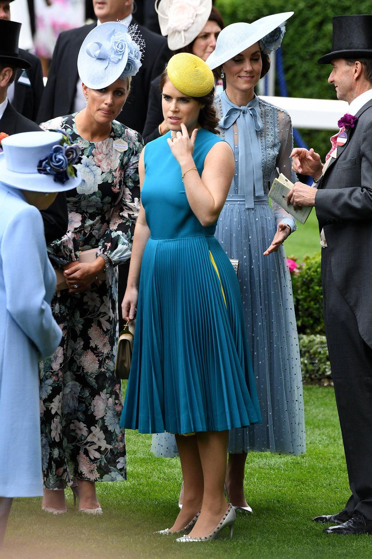 Prinzessin Eugenie hat Faszinator und Kleid perfekt aufeinander abgestimmt. Der Gelbton ihrer Kopfbedeckung findet sich im plissierten Rock ihres Kleides wieder.