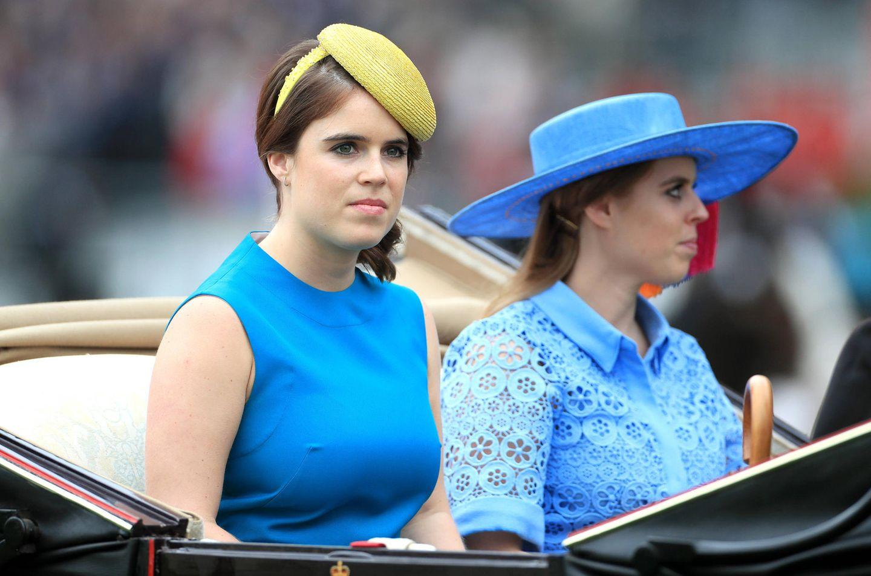 Prinzessin Eugenie und Prinzessin Beatrice sitzen in der vierten Kutsche. Auch sie setzen an diesem Tag auf Blau. Während Eugenie einen gelben Faszinator wählt, trägt Beatrice einen blauen Hut mit breiter Krempe.