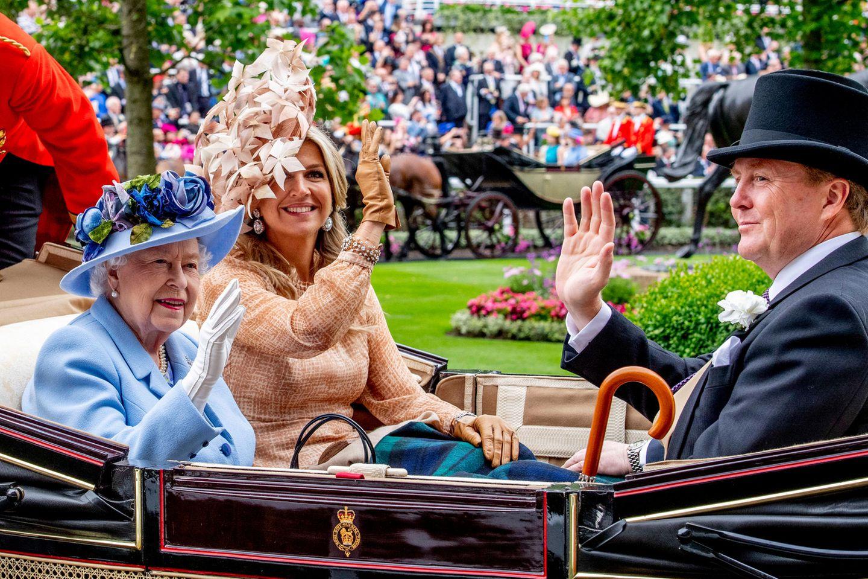 """Hinter dem opulenten Faszinator verbirgt sich Königin Máxima, die zusammen mit ihrem Ehemann, König Willem-Alexander (rechts), in einer Kutsche mit der Queen an der """"Royal Procession"""" teilnimmt und strahlend den vielen Zuschauern winkt."""