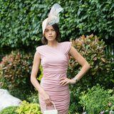 Model Georgia Fowler setzt ihre tolle Figur in einem rosafarbenen, gerafften Kleid in Szene. Dazu trägt sie natürlich eine Kopfbedeckung. Spitze Pumps und ein kleines Handtäschchen runden den Look ab.