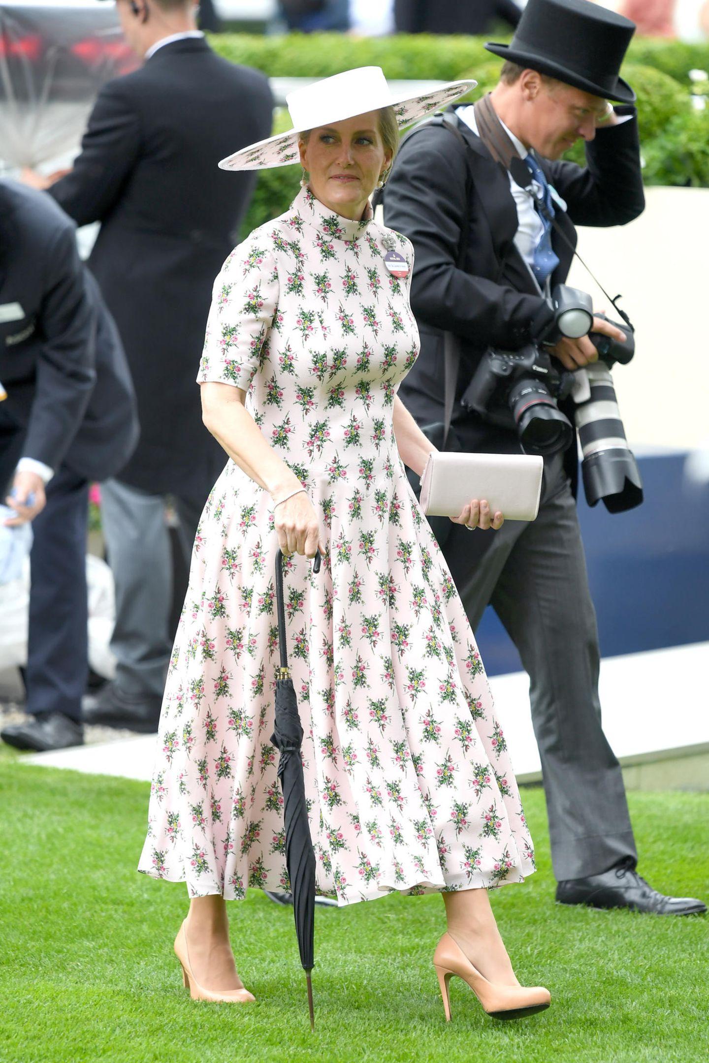 Sophie, Gräfin von Wessex, setzt auf ein weißes Midi-Dress mit Muster. Der hochgeschlossene Schnitt, die betonte Taille und der ausgestellte Rock stehen ihr super.