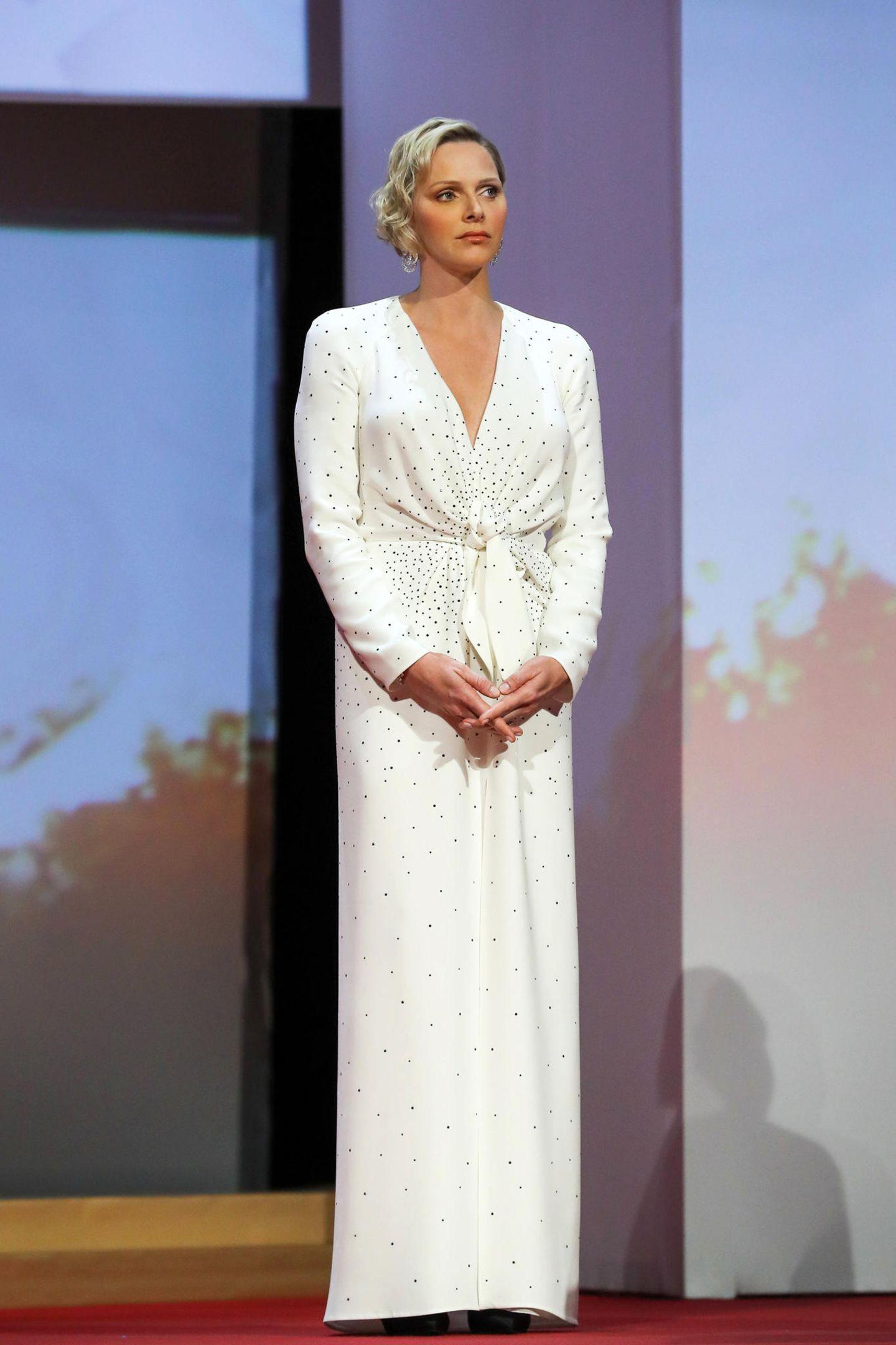 Fürstin Charlène trägt ein bodenlanges, weißes Kleid mit V-Ausschnitt, geraffter Taille und schwarzen, filigranen Punkten. Das Modell stammt aus der Pre Fall Kollektion von Louis Vuitton.