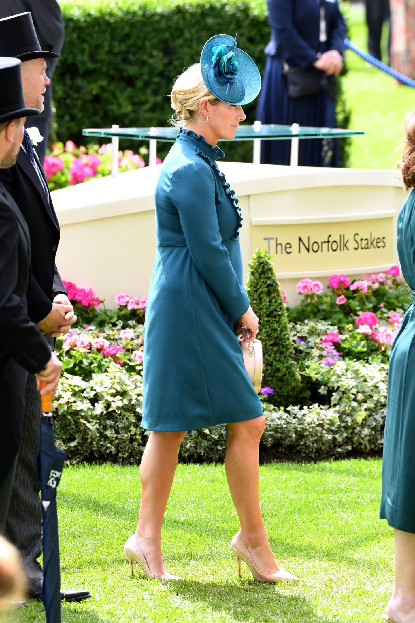 Zara Phillips macht in ihrem petrolfarbenen Kleid eine tolle Figur. Laut Ascot-Dresscode wäre ihr Look eigentlich zu kurz, der hochgeschlossene Ausschnitt mit Rüschenlenkt jedoch einige Blicke auf sich.