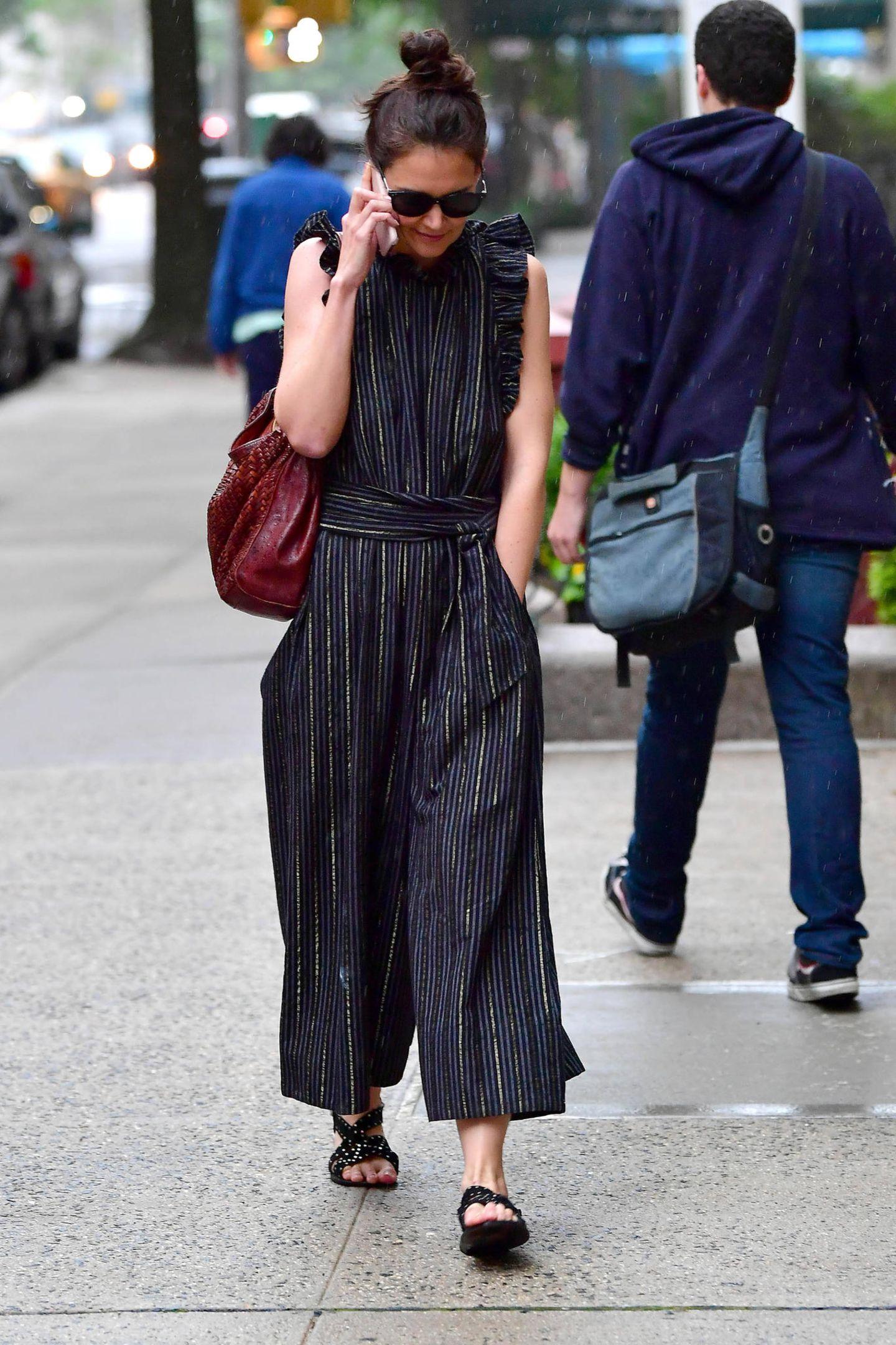 In einem plissierten Einteiler macht Katie Holmes eine tolle Figur. Dazu kombiniert sie XL-Sonnenbrille, flache Sandalen und eine braun-rote Tasche. Kleine Rüschen am Oberteil und ein breiter Gürtel an der Taille verleihen dem Look zusätzlich das feminine Etwas.