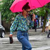 Es sieht aus, als würde die Schauspielerin in diesem Moment ihre Schuhwahl bereuen: Sie trägt weiße Riemchen-Heels, die sie zu einer coolen Jeans und einer geblümten Bluse kombiniert.