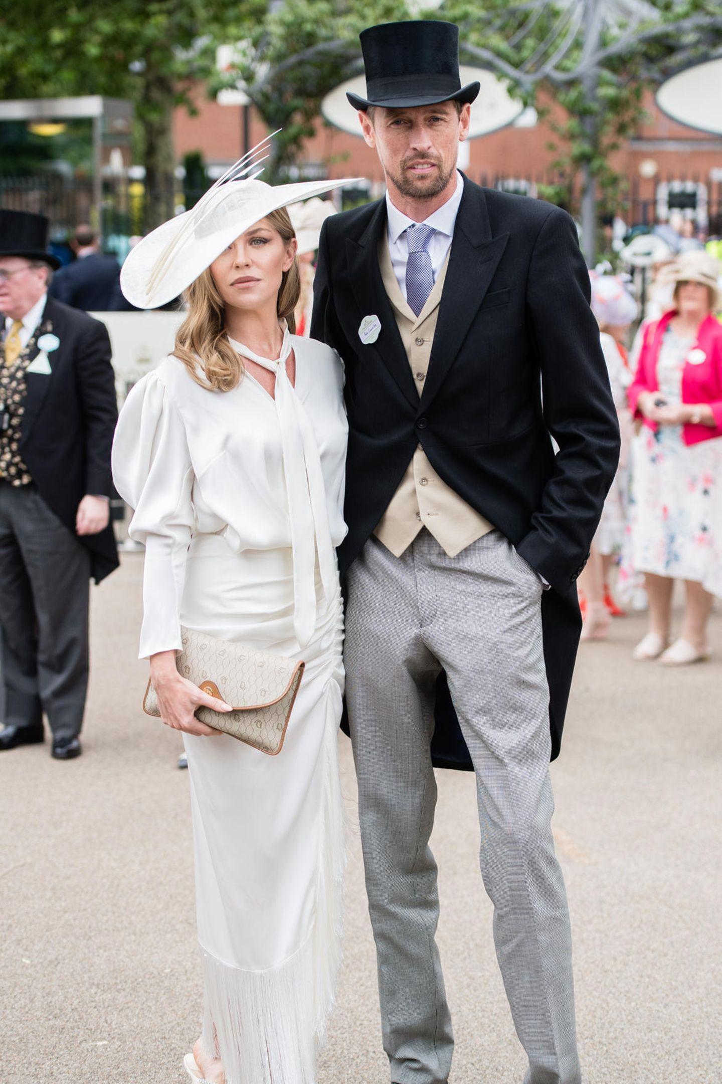Abbey Clancy und Peter Crouch geben ein tolles Bild ab. Der Fußballer und seine Frau posieren Arm in Arm für die Fotografen. Sie trägt ein weißes bodenlanges Kleid mit passender Kopfbedeckung, er setzt auf einen klassischen Frack.