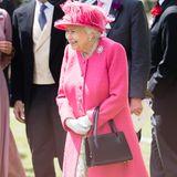 Die Queen zeigt sich in Pink und strahlt. Hut und Mantel sind farblich perfekt aufeinander abgestimmt. Darunter trägt sie ein geblümtes Kleid und auffälligen Schmuck.