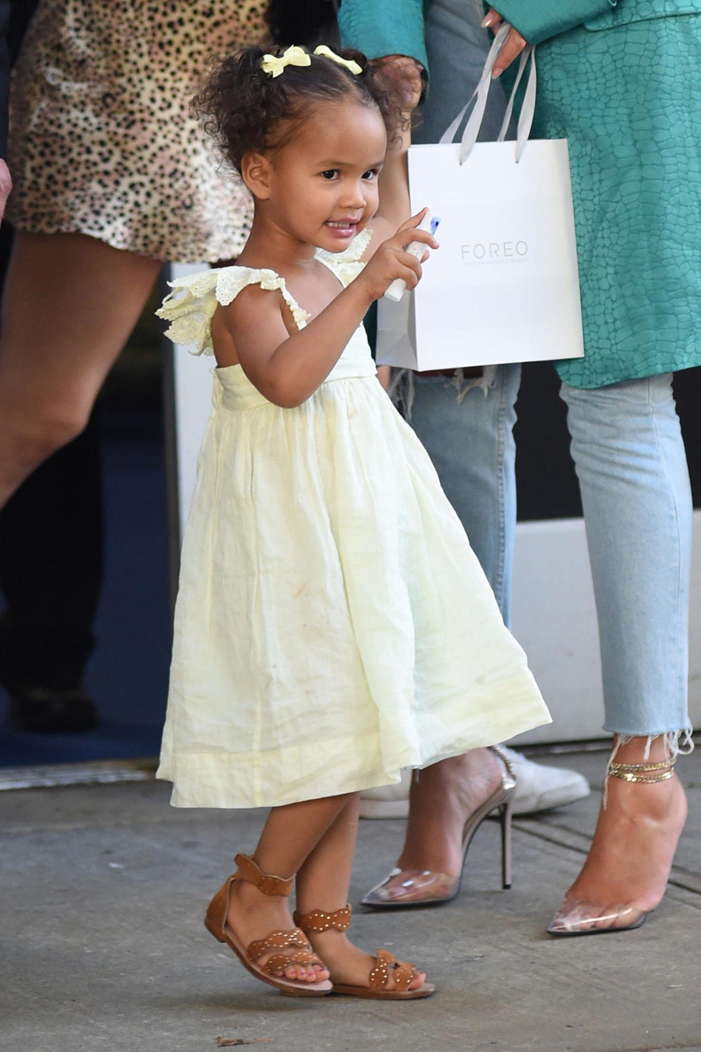 Zu ihren braunen Schuhen trägt Luna ein hellgelbes Kleid mit Rüschenträgern und zwei dazu passende Schleifen im Haar. Einfach zuckersüß!